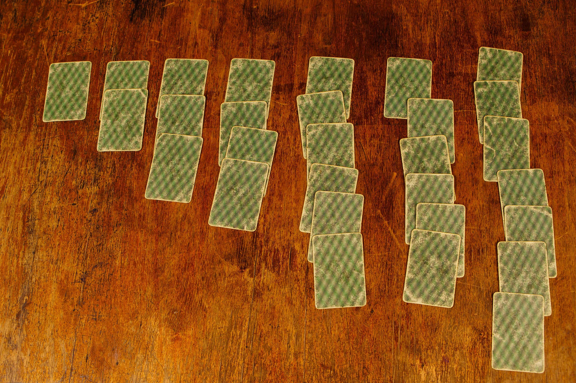 solitaire of playing cards on a wooden table